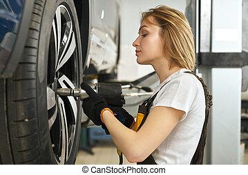junge frau, reparatur, auto, radkappe, gebrauchend, tool.