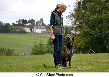 Junge Frau trainiert mit Hund - Hundeausbildnerin mit einem ...