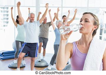 junge frau, trinkwasser, mit, leute, dehnen, hände, in, der, hintergrund, an, fitnesstudio