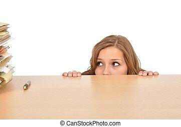 Junge Frau versteckt sich hinter dem Schreibtisch