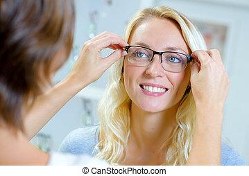 junge frau, versuchen gläsern, in, optisch, kaufmannsladen