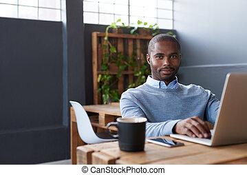 junger, afrikanisch, geschäftsmann, arbeiten, a, laptop, in, ein, buero