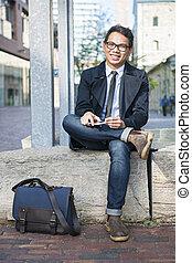 junger, asiatischer mann, sitzen draußen