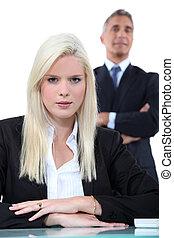 junger, blond, geschäftsfrau, mit, älterer mann, in, der, hintergrund