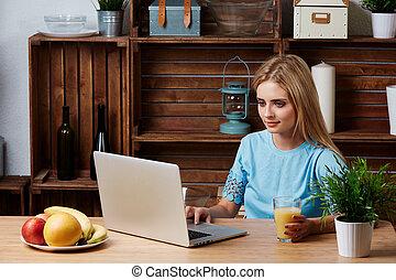 junger, blond, woman, aussieht, für, a, rezept, informationen, auf, laptop-computer, heim, kitchen., machen diät, concept.