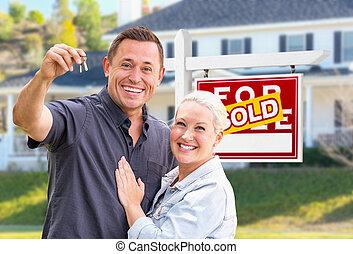junger erwachsener, paar, mit, bringen schlüssel, vor, daheim, und, verkauft, verkauf, immobilien- zeichen