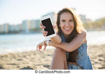 junger, glückliche frau, sitzen strand, ausstellung, smartphone