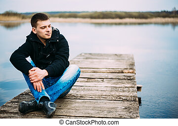 junger, hübsch, mann sitzen, auf, hölzerner pier, entspannend, denken,