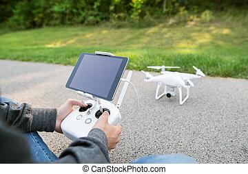 junger, hüfthose, mann, mit, fliegendes, drone., sonnig, grün, nature.