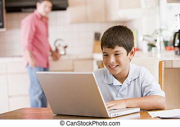 junger junge, in, kueche , mit, laptop, und, schreibarbeit, lächeln, mit, mann, in, hintergrund