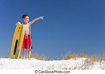 junger junge, kind, auf, a, sandstrand, mit, surfbrett, zeigen