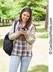 junger, lächeln, schueler, gebrauchend, a, smartphone