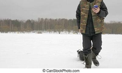 junger mann, auf, a, frozen lake, mit, a, telefon, sehen,...