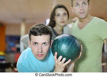 junger mann, bereitet, zu, werfen, von, grüne kugel, in, bowling;, mann frau, blick, away;, fokus, auf, links, man;, seicht, schärfentiefe