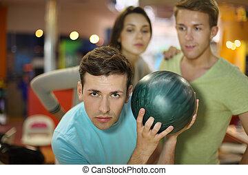 junger mann, bereitet, zu, werfen, von, kugel, in, bowling;, mann frau, betrachten, him;, fokus, auf, links, man;, seicht, schärfentiefe