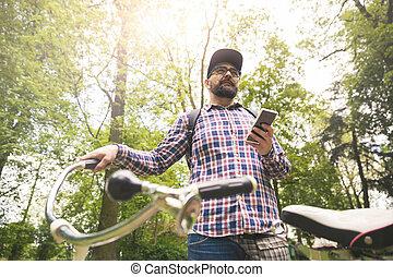 junger mann, besitz, fahrrad, und, smartphone, an, park