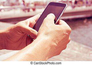 junger mann, gebrauchend, a, smartphone, draußen, mit, a, filter, effekt