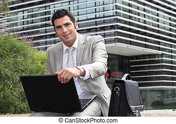 junger mann, laptop benutzend, draußen