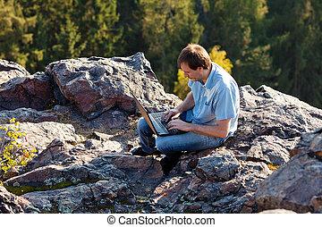 junger mann, laptop benutzend, sitzen, auf, a, gestein, steigung