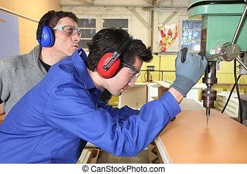 junger mann, lernen, wie, zu, gebrauch, a, bohrgerät- presse