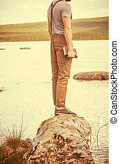 junger mann, mit, buch, stehende , draußen, mit, see, hintergrund, sommer, urlaube, und, lebensstil, begriff, retro, farben
