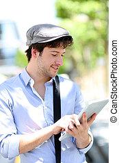 junger mann, mit, hut, gebrauchend, digital tablette, in, stadt