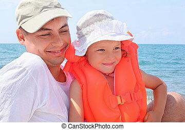 junger mann, mit, kleines mädchen, in, orange, lifejacket, auf, sandstrand