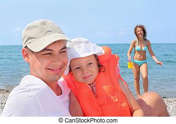 junger mann, mit, kleines mädchen, in, orange, lifejacket, und, schöne frau, mit, plastik spielzeug, wischeimer, auf, sandstrand