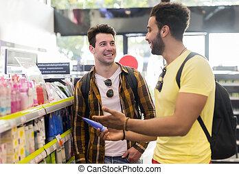 junger mann, paar, in, supermarkt, wählen, produkte, glückliches lächeln, typen, kaufen
