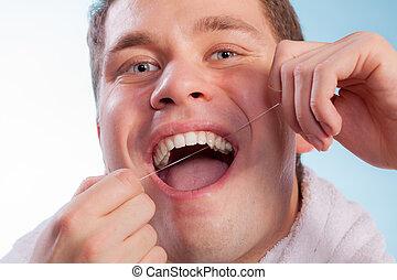 junger mann, putzen, sie, weiße zähne, mit, zahnseide