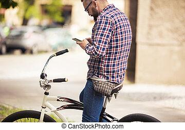 junger mann, sitzen, auf, fahrrad, gebrauchend, beweglich