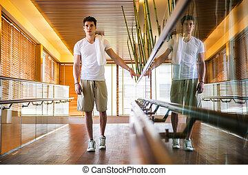 junger mann, stehen gang, halten hand, schiene