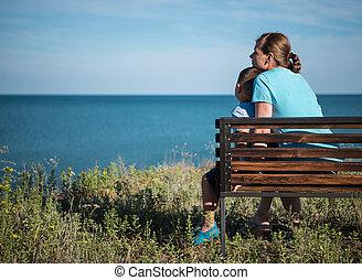 junger, mutter, kind, sitzen, bank, bei, der, meer, ocean.
