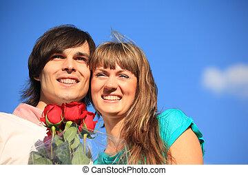 junger, paar, mit, strauß rosen, gegen, himmelsgewölbe