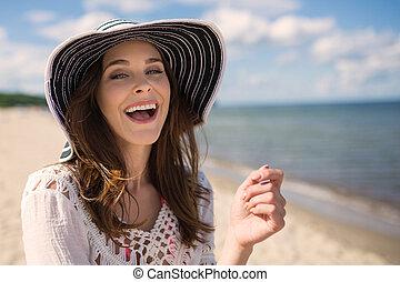 junger, schöne frau, in, hut, stehende , auf, sandstrand, lächeln