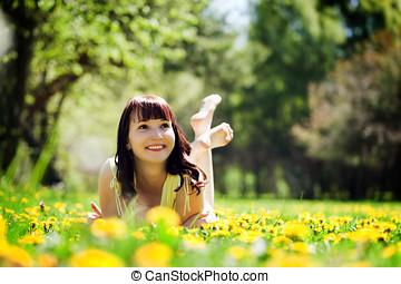 junger, schöne frau, lügen gras, voll, von, frühjahrsblumen, und, lächeln.