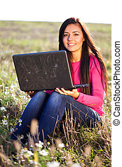 junger, schöne frau, mit, a, laptop, sitzen, in, der, feld, auf, himmelsgewölbe, hintergrund