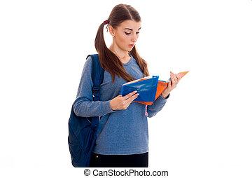 junger, schöne , schueler, m�dchen, mit, rucksack, liest, a, buch, und, posierend, freigestellt, weiß, hintergrund, in, studio