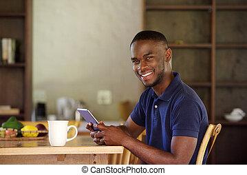 junger, schwarz, kerl, sitzen, hause, mit, a, digital tablette