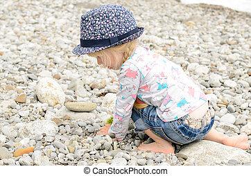 junges mädchen, spielende , mit, steine, strand
