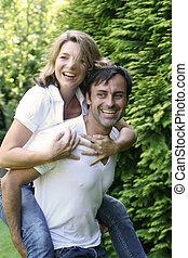 Junges Paar hat Spass in der Natur Der Mann tr�gt die Frau...