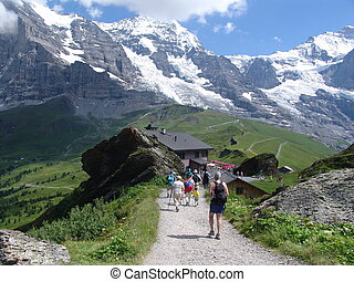 A view of some hikers hiking in the Jungfrau region of the Bernese Oberland, near Interlaken, Switzerland