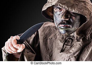 Jungle combat - a soldier wearing a poncho or raincoat and...