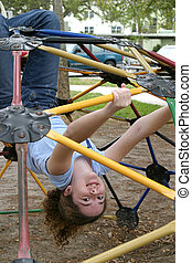 Jungle Gym Girl 1 - A girl swinging upside down from a...