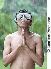 Jungle rain prayer - Young Asian man with goggles portrait,...