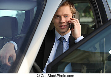 junior executive on the phone driving luxury car