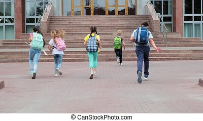 junior schoolchildren with backpacks run to school building...