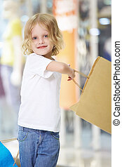 Junior shopaholic - The little girl waving bags at the store