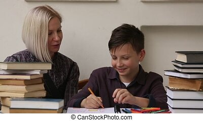 Junior student does homework with the help of his tutor.