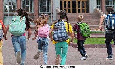 junior students with schoolbags walk to school building - ...